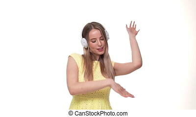 Excited woman in headphones listening to the music, slow motion, isolated on white studio background.