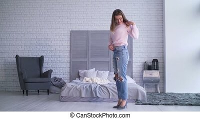 Excited woman in loose jeans after losing weight