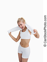 Excited woman in sportswear holding towel around neck