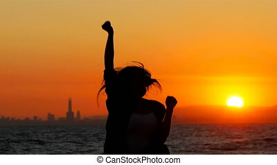 Excited woman jumping at sunset celebrating success -...