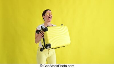 Excited woman jumping with a suitcase on a yellow background.