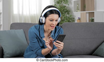 Excited woman listening to music online sitting on a couch...