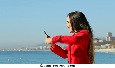 Excited woman on phone on the beach in winter slow motion -...