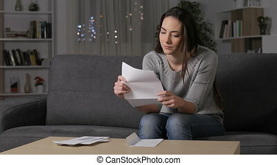 Excited woman reading good news on letter sitting on a couch...