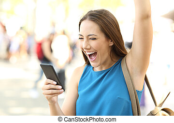 Excited woman receiving good news on phone