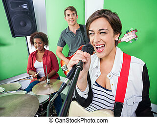 Excited Woman Singing While Band Playing Musical Instrument