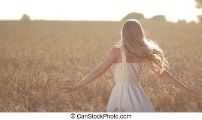 Excited woman spinning in wheat field at sunset