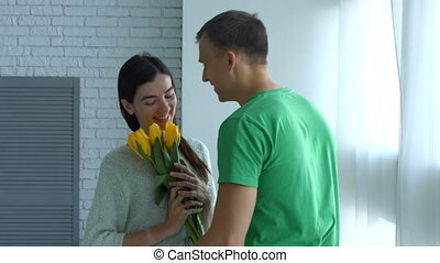 Excited woman surprised by bunch of flowers from man