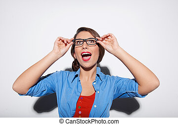 Excited woman. Surprised young woman adjusting glasses and looking up while isolated on white