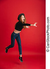 Photo of young excited woman try to grab something isolated over red background. Looking aside.