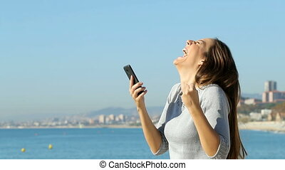 Excited woman using a smart phone in slow motion - Profile...