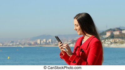 Excited woman using phone on the beach in winter - Side view...
