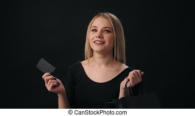 Excited cheerful woman with blond hair looking forward for black friday sale. Happy lady posing over black background with shopping bags and credit card.
