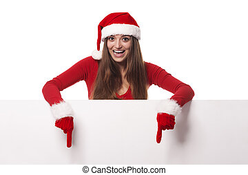 Excited woman wearing santa hat showing on blank billboard