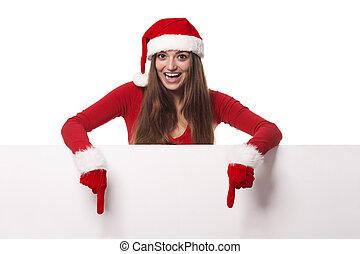 Excited woman wearing santa hat showing on blank billboard
