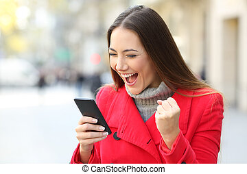 Excited woman winning on line on the street in winter