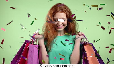 Excited woman with colorful paper bags after shopping jumping over confetti rain in studio background. Concept of seasonal sale, purchases, spending money on gifts. High quality 4k footage