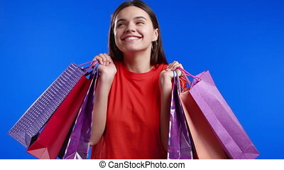 Excited woman with colorful paper bags after shopping on blue studio background. Concept of seasonal sale, purchases, spending money on gifts. High quality 4k footage