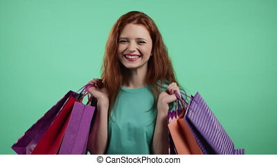 Excited woman with colorful paper bags after shopping on green studio background. Concept of seasonal sale, purchases, spending money on gifts. High quality 4k footage