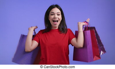 Excited woman with colorful paper bags after shopping on violet studio background. Concept of seasonal sale, purchases, spending money on gifts. High quality 4k footage