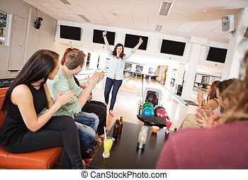 Excited Woman With Friends Applauding - Young woman standing...