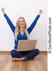 Excited woman with laptop sitting on floor