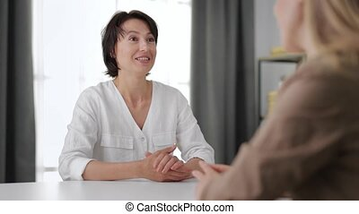 Two excited women in casual clothes sitting together at table and chatting at home. Happy female friends spending leisure time indoors. Secret talks.