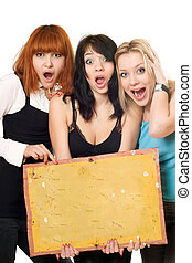 Excited women holding a board - Three young excited women...