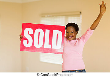 young african american woman with sold sign