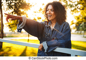 Excited young african girl in denim jacket