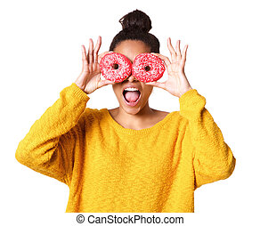 Excited young african woman covering her eyes with donuts