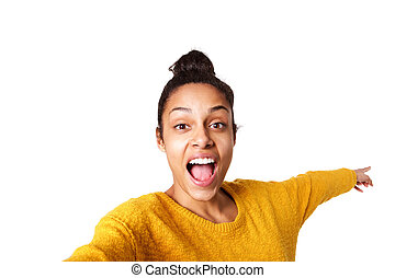 Excited young african woman pointing back and taking selfie