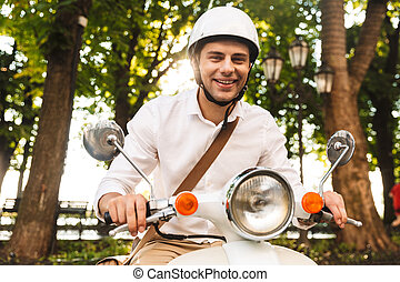 Excited young businessman riding on a motorbike