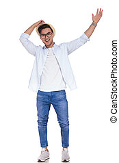 excited young casual man with hands up celebrating success