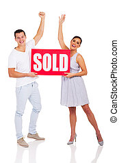 excited young couple holding sold sign