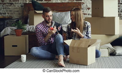 Excited young couple is unpacking things, opening box, taking personal items and talking after moving to new apartment. Relationship and relocation concept.