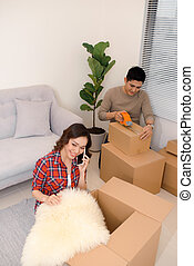 Excited young couple unpacking carton boxes with cozy home stuff in new apartment.