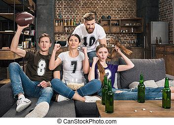 friends watching football match at home
