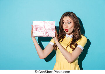 Excited young girl in dress looking at a present box