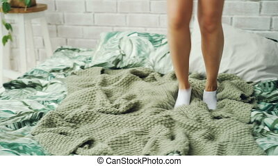 Excited young lady is dancing on bed and singing wearing...