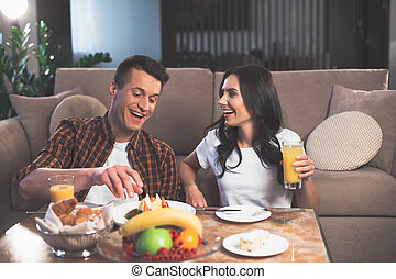 Excited young man and woman eating sweet food indoors