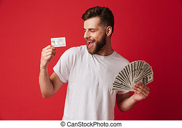 Excited young man holding money and credit card.