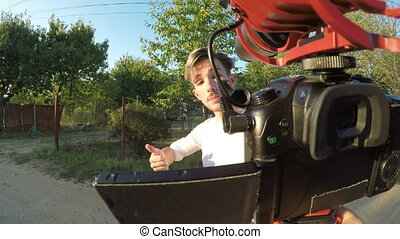 Excited young man spinning and recording a video outside his...