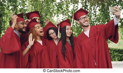 Excited young people graduates are taking selfie with...