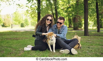 Excited young people loving couple are fussing cute dog...