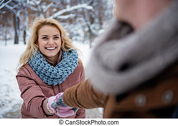 Excited young woman having fun with man in park