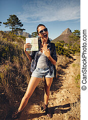 Excited young woman hiker showing a map