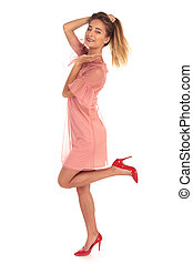 excited young woman holding her hair and one leg up