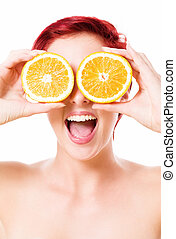 excited young woman holding oranges over her eyes