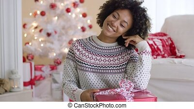 Excited young woman holding up a Christmas gift